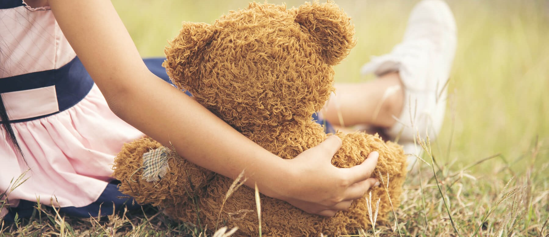 Girl Hugging Teddy on Grass